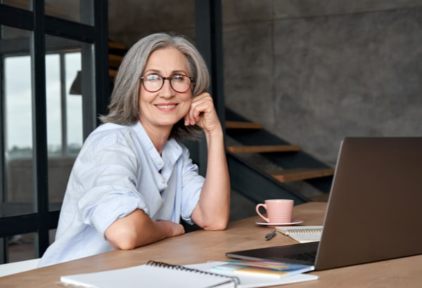 Middle aged woman sits at desk with laptop