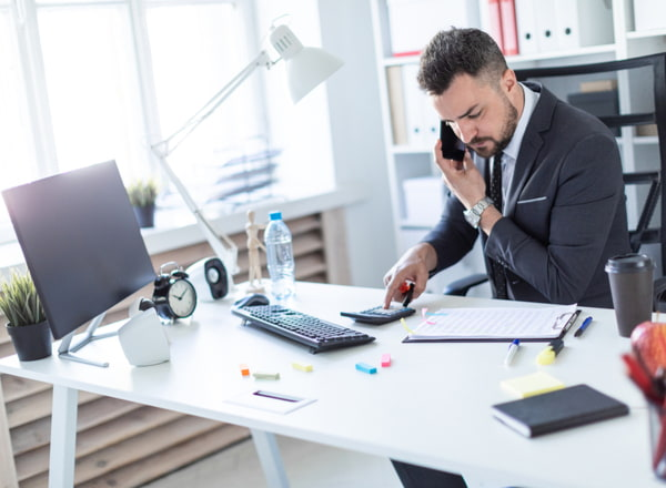 A man is sitting at the desk at the office talking on the phone