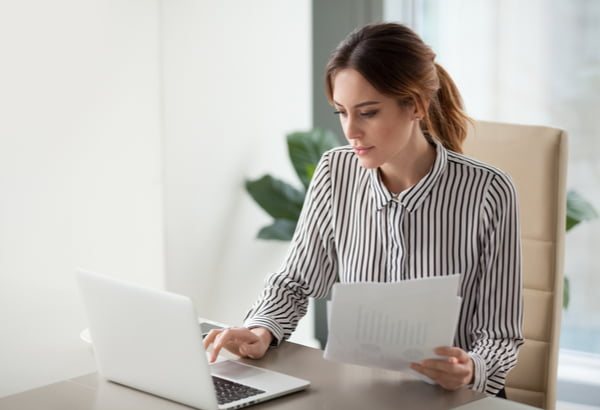Focused businesswoman typing on laptop holding papers