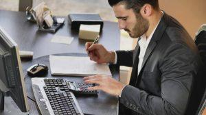 Man in formal wear working as accountant at desktop