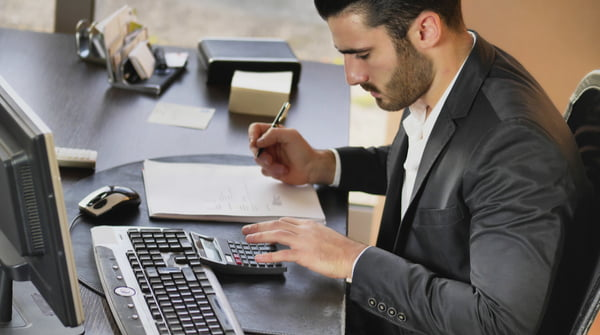 Man in formal wear working as accountant at desktop