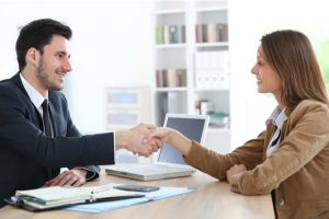 Woman giving handshake to financial adviser