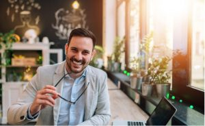 Entrepreneur holding eyeglasses while smiling at the camera