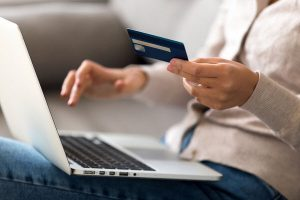 Woman using a credit card while in her laptop