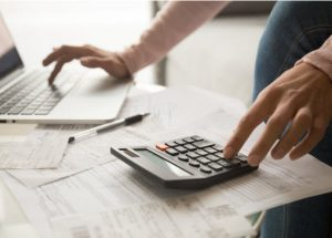 Young woman calculating monthly expenses