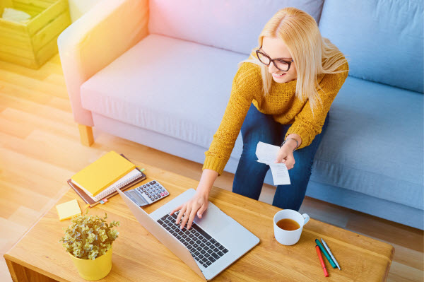Happy young woman paying bills on laptop while sitting on sofa
