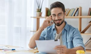 Happy young unexperienced male prepares business report