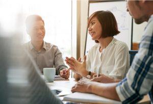 Female entrepreneur talking to her employees at meeting