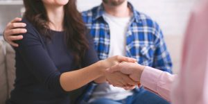 Thankful couple handshaking with specialist