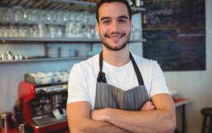 Confident young waiter with arms crossed