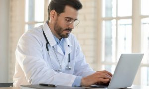 Young physician using his laptop