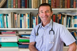 Happy doctor in front of a book shelf full of Medical books