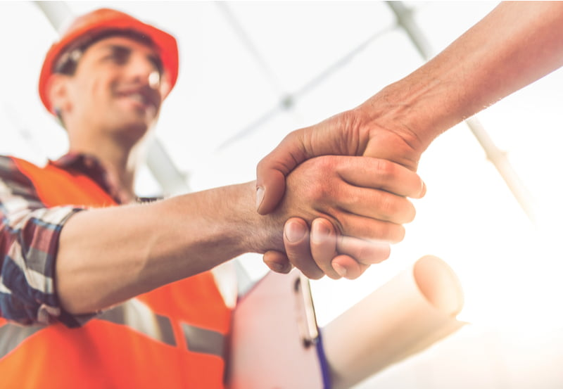 Construction workers in protective helmets and vests are shaking hands