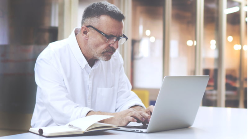 Mature businessman in eye glasses using his laptop