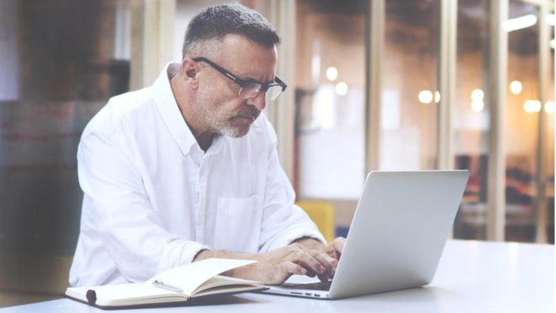 Mature businessman in eye glasses using his laptop