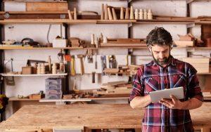 Carpenter standing in his workshop using a digital tablet