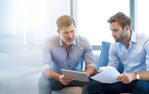 Businessman using a digital tablet to discuss information with a younger colleague