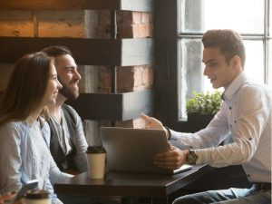 Salesman making offer to young millennial couple