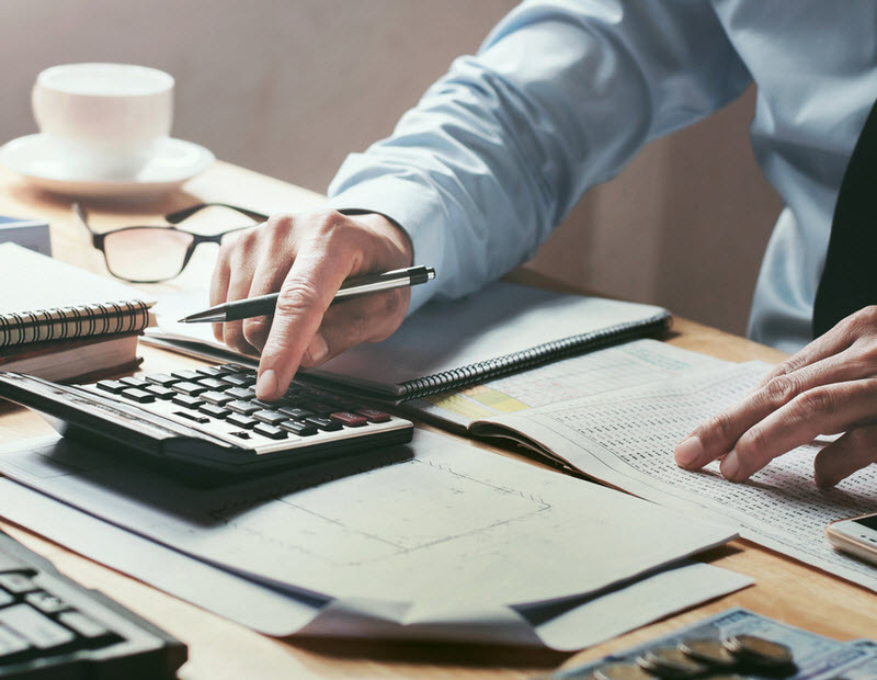 Man working on his desk, calculating financial report