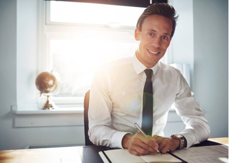 Business man wearing a corporate attire writing notes while smiling at the camera
