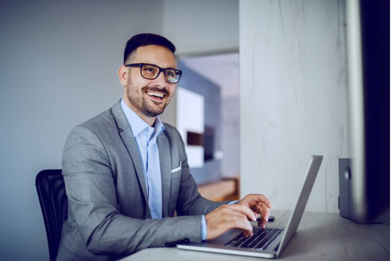 Smiling man wearing a corporate attire while using his laptop