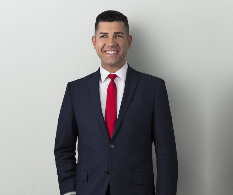 Man wearing coat and tie smiling at the camera
