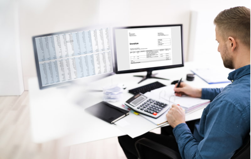 Businessman calculating bill with computer and calculator