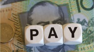 Pay signage with a background of Australian money