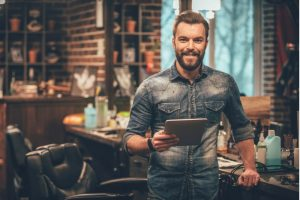Bearded man looking at camera and holding digital tablet