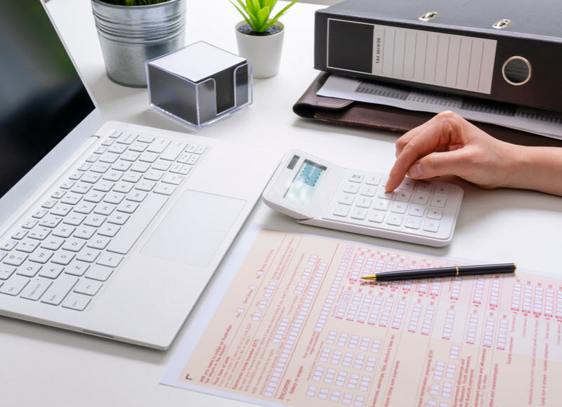 woman using a calculator filling up the Tax form