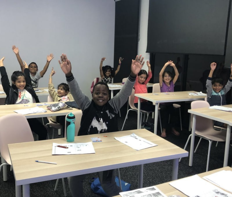 A group of students raising their hands