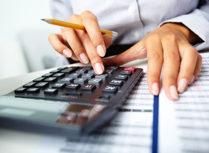 Photo of hands holding pencil and pressing calculator