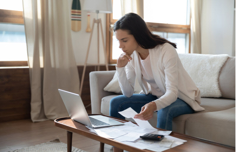 Woman checking on bills, receipts while looking at the laptop