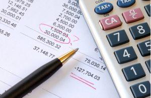 Sheet of financial report, pen and calculator
