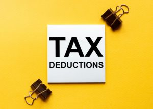 White paper with text Tax Deductions on a yellow background